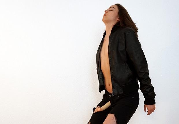 Julia B. Laperrière ist von der Seite zu sehen, sie steht mit geschlossenen Augen in sich hineinspürend da, den Kopf leicht nach hinten geneigt, die Augen geschlossen. Ihre Knie sind gebeugt, die hängenden Arme leicht nach hinten gezogen. Die schwarze Lederjacke ist vorne offen und gibt den Blick auf die Mittelachse des nackten Oberkörpers frei. Die Brust wirkt flach und aus dem pffenen Reißverschluss der ebenfalls schwatzen Hose ragt ein Dildo in der Form eines lebensechten, errigierten Penis'.